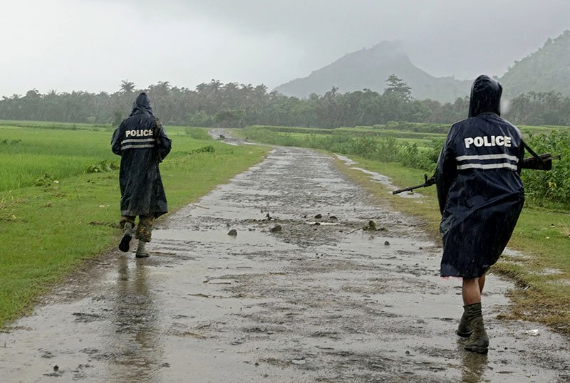 Myanmar police officers in rain coats patrol on a road in the etnic Rakhine village of ChainKharLi, an area close to fighting at Rathedaung township of northern Rakhine State, western Myanmar. Photo : Mizzima News