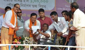 Chief Minister Sarbananda Sonowal handing over his 'letter of contribution' as part of 'Daan Toilet' initiative for construction of a toilet for a differently-abled person during the inaugural programme of 'Mission Sambhav' at Jagiroad in Morigaon.