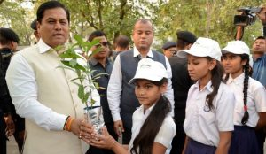 CM Sarbananda Sonowal distributing saplings to students during the celebration of International Day of Forest.