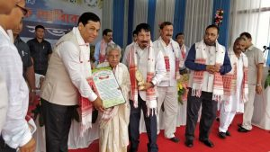 Chief Minister Sarbananda Sonowal felicitating wives of the late founding members of Sadou Asom Khudra Chah Khetiyok Santha at the 10th Triennial State Conference of the Santha at Golaghat.