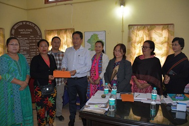 NCHAC Executive Member in-charge of medical department Samuel Changsan distributing Atal Amrit Abhiyan demand drafts to beneficiaries at office chamber of Joint Director of Health Services in Haflong on May 11, 2018. A DIPRO photo