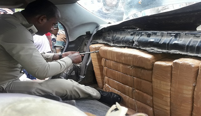 Packets of ganja concealed in the back seat of  car being recovered by Tripura Police on July 19, 2018. Photo: Panna Ghosh