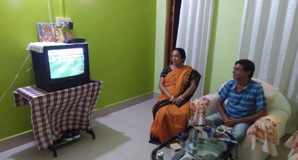 Prodip Das, a bronze medellist at Seoul Asiad in 1986 watching with his wife the ongoing Asiad Games at Jakarta at his residence in Silchar