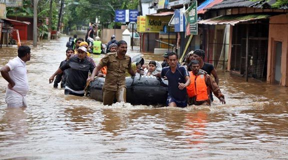 Rescuers evacuate people from a flooded area to a safer place in Aluva in  Kerala.