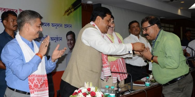 File photo of Assam CM Sarbananda Sonowal handing out accreditation card to journalist at a programme held at Assam Administrative Staff College in Guwahati on Wednesday.  Image credit: UB Photos