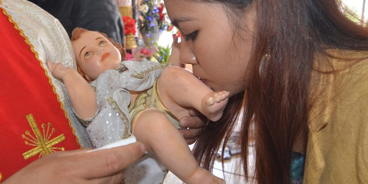 A girl kisses a statue of baby Jesus after Christmas prayers in Guwahati on Tuesday. Image credit: UB Photos