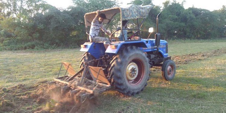 Tractor busy in preparing land for potato farming