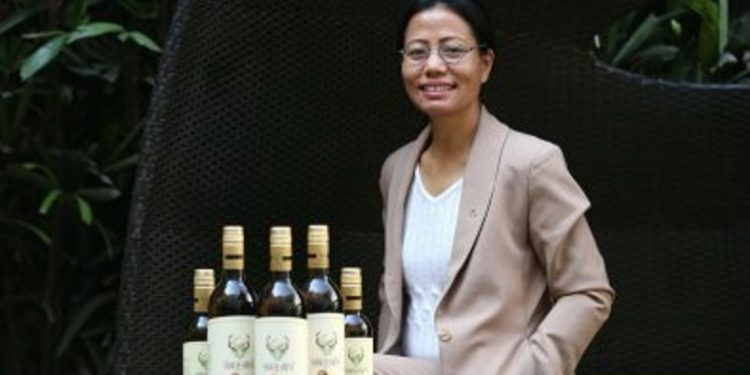 Entrepreneur Tage Rita Takhe with the country's first Kiwi wine Naara-Aaba Image Credit: garimashares.com