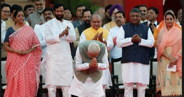 Prime Minister Narendra Modi greets the crowd during a swearing-in ceremony.