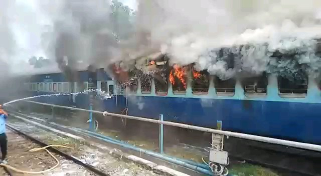 Localites dousing flames of a train in Silchar railway station on Sunday (1)