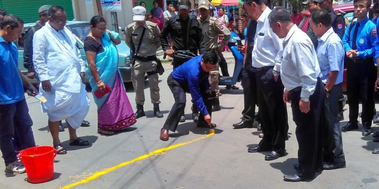 manipur health minister L Jayentakumar looks on while health director k rajo was painting yellow line during yellow line campaign launching session as part of world no tobacco day in Imphal on friday