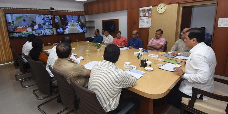 Assam chief minister Sarbananda Sonowal reviewing flood situation prevailing in the state and interacting with the DC and other concerned functionaries through video-conferencing in Guwahati on Thursday.