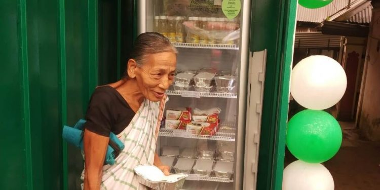 An old woman collecting food from the community fridge in Jorhat on Sunday.