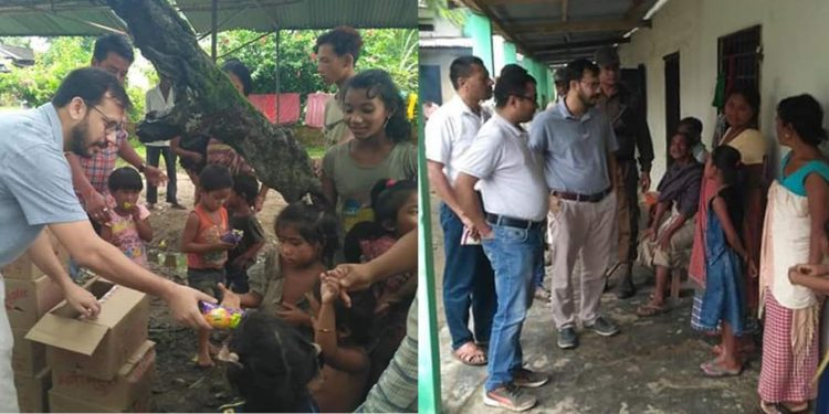 Dibrugarh deputy commissioner Pallav Gopal Jha distributes food among flood affected children in a relief camp and meets flood affected people in different relief camps. Image credit - Northeast Now