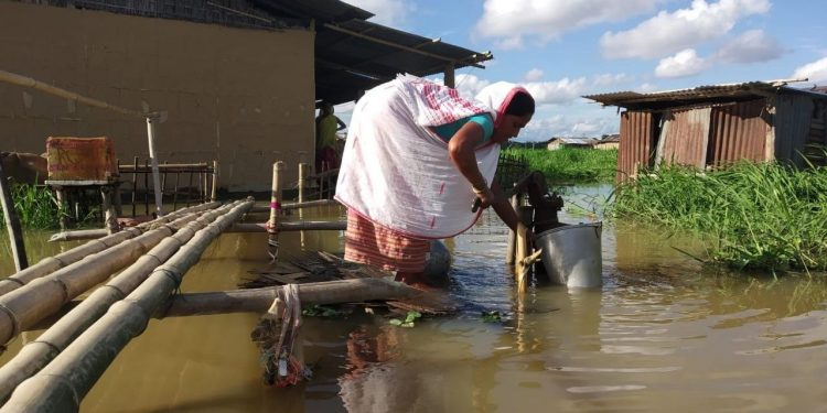 A woman collecting drinking water from a tube-well submerged with flood water.