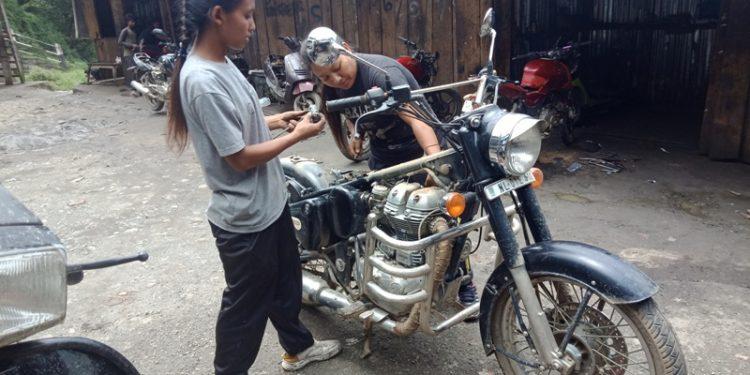 Pongam N. Konyak and W. Nginlei Konyak repairing a bike at a garage in Kohima.