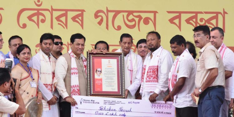 Assam CM Sarbananda Sonowal presenting the Sonit Konwar Gajen Barua Award 2019 to noted dramatist Bhaben Bora in Jamugurihat. Image credit: UB Photos