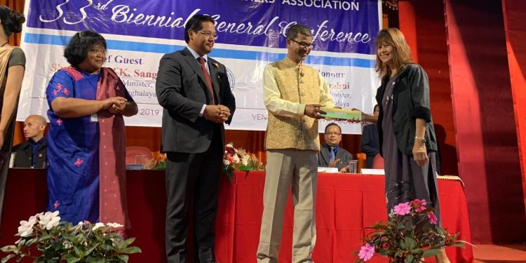 Meghalaya education minister Lahkmen Rymbui giving away a memento to a teacher at the event in Shillong on Friday.