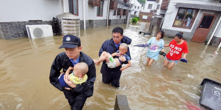 Policemen helping people stranded by floods in Zhoushan City in China.