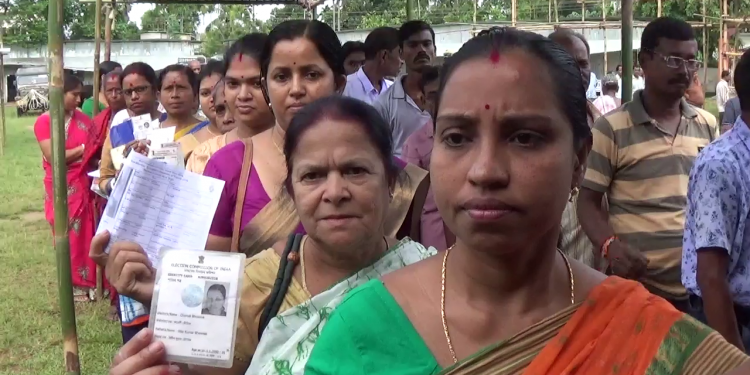 Voters standing in a queue to cast their votes at a polling booth in Tripura's Badharghat (SC) assembly constituency on Monday.