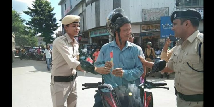 Police personnel offering rose to traffic abiders at Tangla town in Udalguri on Thursday. Image: Northeast Now