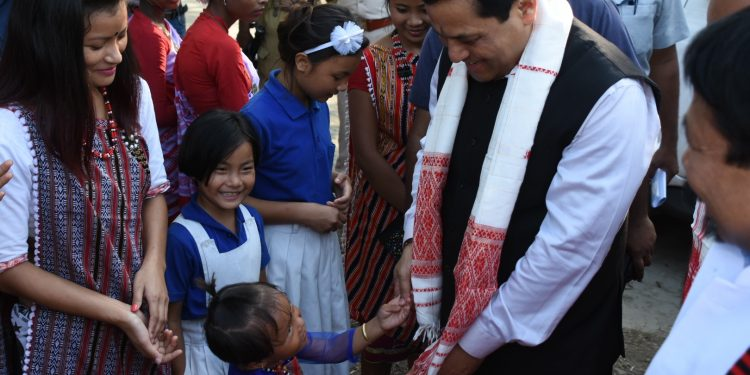 Assam CM Sarbananda Sonowal speaking to a kid during the opening of Kaziranga National Park at Bagori on Saturday.
