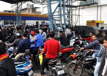 People queue in a petrol pump after curfew was relaxed in Guwahati for 7 hours on Saturday. Image credit: Hindustan Times