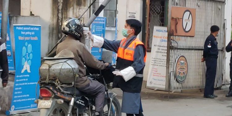 Health officials using infrared forehead thermal screening equipment to screen visitors on in Darrangamela entry point of eastern Bhutan's Samdrup Jongkhar district's bordering Baksa district of Assam.