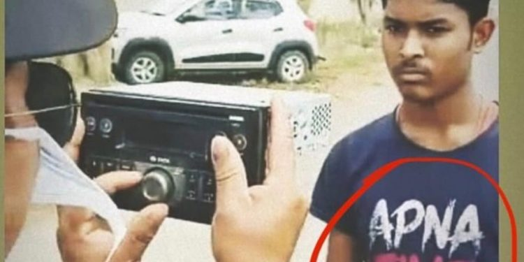 A migrant worker being screened for coronavirus by a car tape recorder.