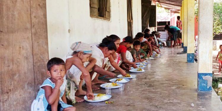 Children and women having food at Baghjan relief center on Thursday.