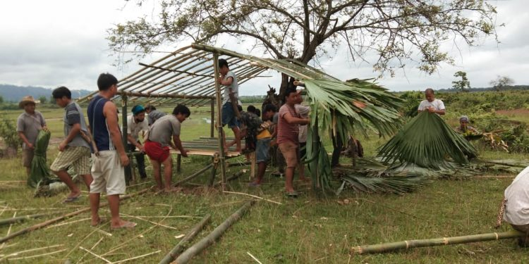 Villagers building the huts.