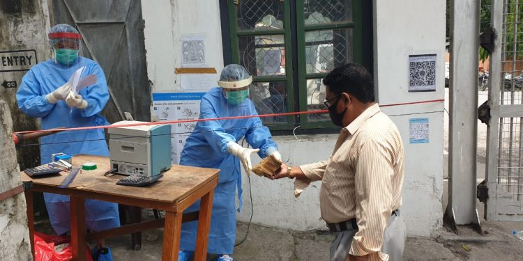 Bank of Bhutan officials in PPE kits accepting Bhutan Ngultrums on Monday. Image: Northeast Now