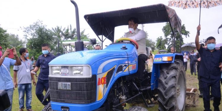 Assam CM Sarbananda Sonowal ploughing with a tractor to prepare a field for cultivation of Kharif crops at Chowkighat in Sonitpur district on Thursday