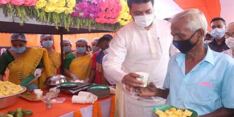 Tripura CM Biplab Deb distributing fruits to the people