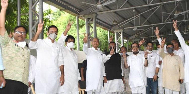 Rajasthan CM Ashok Gehlot flashes the victory sign along with Congress leaders Randeep Singh Surjewala, Ajay Maken and other MLAs at his residence on Monday.