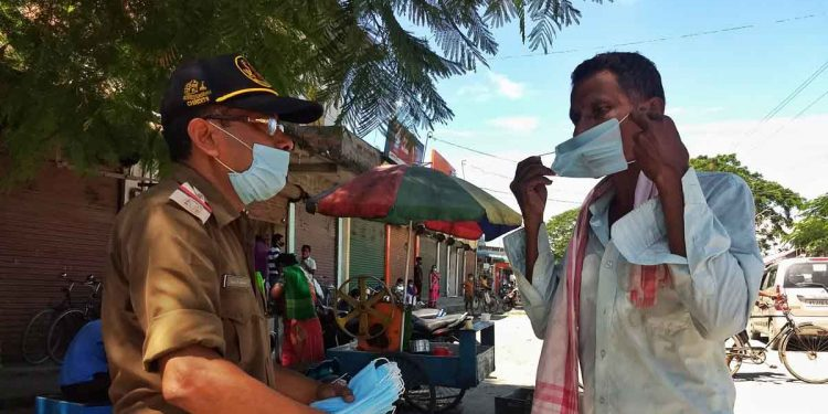 Sub-Inspector Upen Chandra Barman offering masks to citizens at Tangla town. Image: Northeast Now