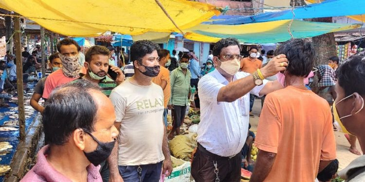 BJP leader Debashish Dutta taking part in a mask distribution programme in Hojai. Image: Northeast Now