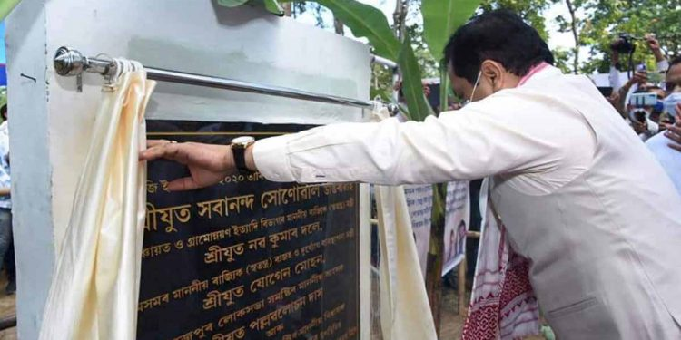 Assam CM Sarbananda Sonowal is unveiling a plaque to mark laying of foundation of a multi-purpose flood shelter home at Dhunaguri in Bihpuria legislative assembly constituency in Lakhimpur