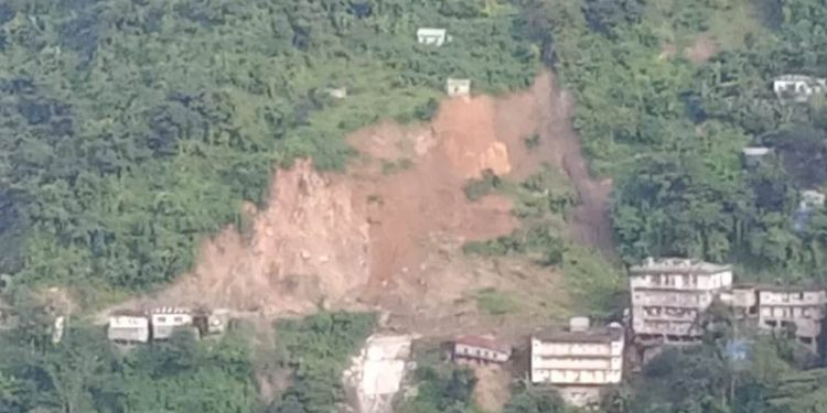 Landslide triggered by rain swept away two buildings, one bus andcar at Aizawl's Zemabawk locality.
