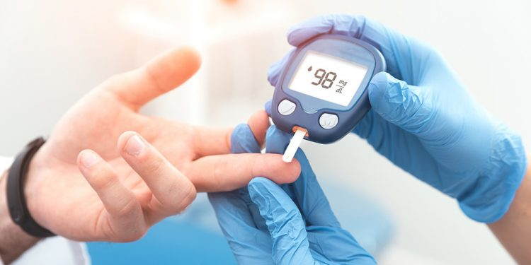 Doctor checking blood sugar level with glucometer.