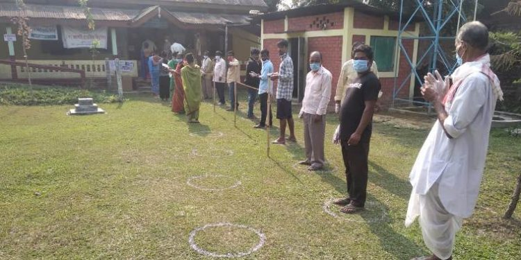 Voters queue up, maintaining social distancing, outside a polling station during the first phase of polling for Assam Assembly elections, at Golaghat district. (File image)