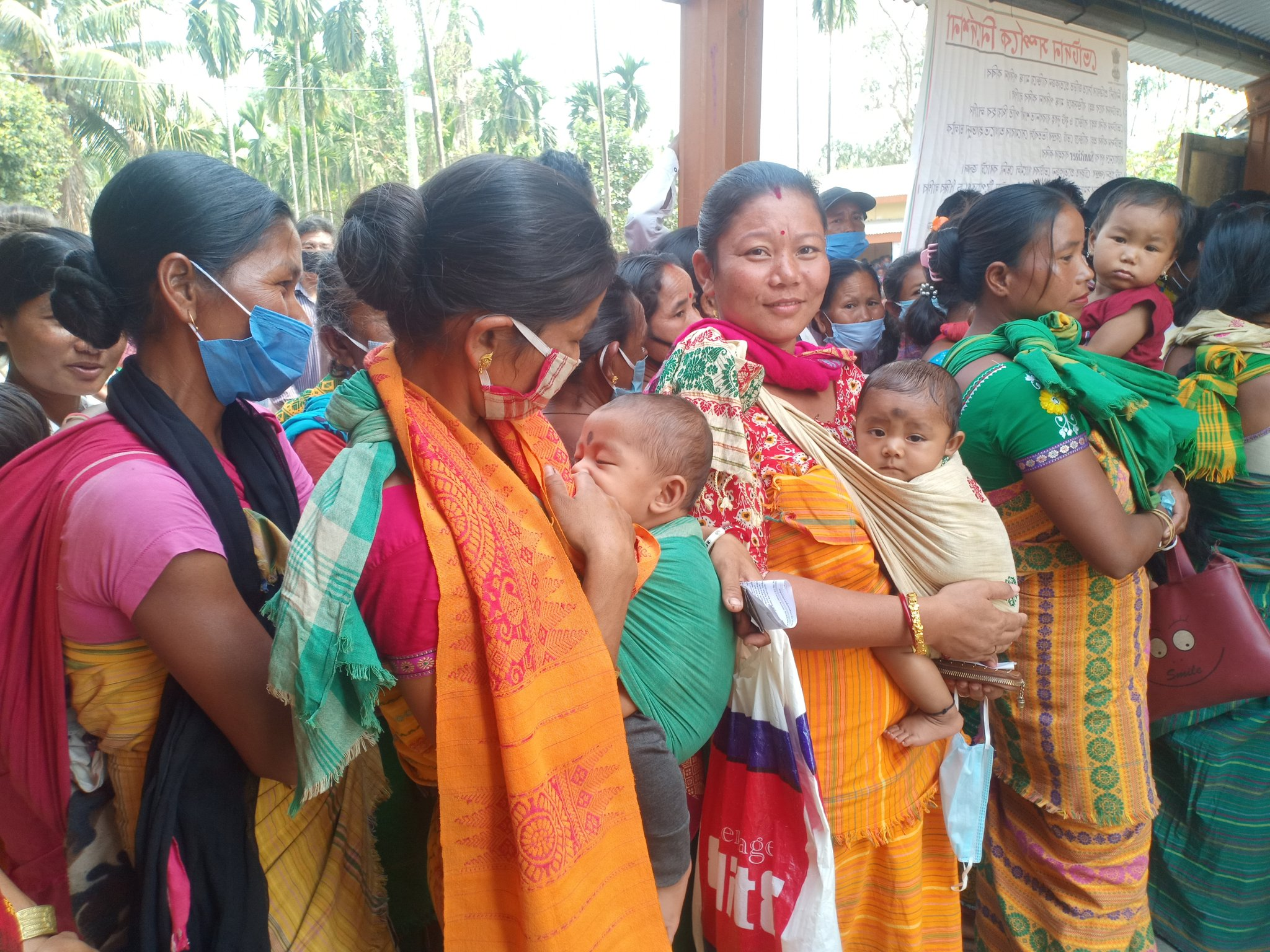 Three women standing in queue with their infants to cast their votes in a polling booth in Biswanath.