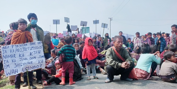 Protesters sit on the road at Mynsang village on to prevent officials from going to Siangkhnai for the public hearing on April 8.