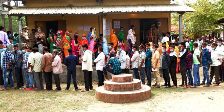 Voters queue up to cast their vote in a polling station in Nalbari district.